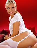 Jenni wearing all white relaxes on her bed.