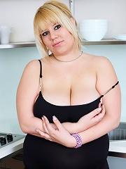 Fresh blondie shows her big melons in the kitchen