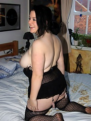 Dark-haired doll licks her own ripe massive boobs