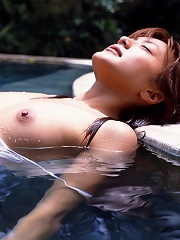 Cute Asian girl goes skinny dipping in the pool under the bright sun and soaks up the rays of the sun.